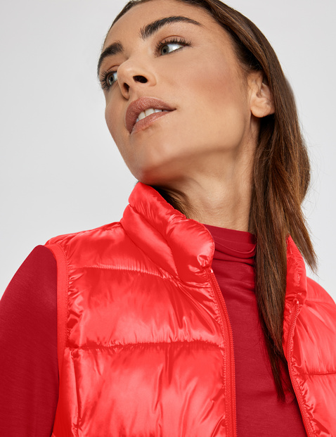 Reversible body warmer with a shiny finish