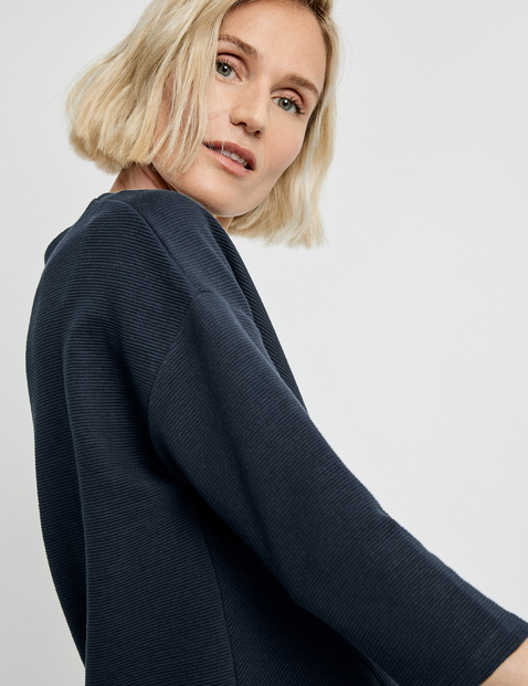 Top with 3/4-length sleeves and a ribbed texture